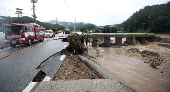 A road in Chungju, North Chungcheong, one of the areas worst affected by the weekend's rains, lies damaged on Sunday. [YONHAP]