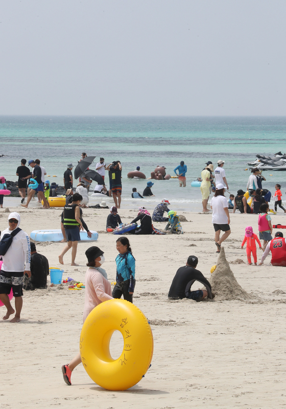 Beachgoers roam around Jeju's Hyeopjae Beach on Monday as a heat wave scorches the southern island. The same day, torrential rainfall soaked Korea's central region. [NEWS1]