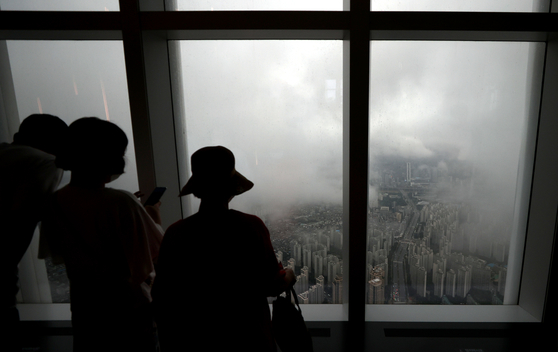 Visitors look at apartments in Jamsil covered in fog from Lotte Tower in Songpa, southern Seoul, on Monday. As the ruling Democratic Party (DP) is planning to push through the government's hike of property taxes with the 176 seats it has in the National Assembly, the government is expected to announce its housing supply plan. Despite the government's efforts, apartment prices in Seoul continued to rise. According to the Korea Appraisal Board, Seoul apartment prices in July rose 1.12 percent compared to June despite the government rolling out new real estate measures. [YONHAP]