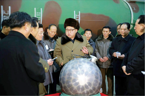 North Korean leader Kim Jong-un, center, poses with what the North claimed was a miniaturized nuclear warhead, in a photograph released by state media in 2016. [RODONG SINMUN]