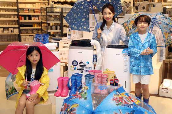 Models promote umbrellas, rain shoes and dehumidifiers, which are selling well during the monsoon season. [EMART]