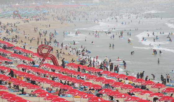 Vacationers cool themselves off at Haeundae Beach in Busan on Tuesday, as a heat wave advisory was issued for the region. [NEWS1]