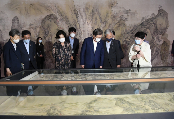 President Moon Jae-in, right, and his wife looking at treasure No. 1986, Chokjandogwon (The Rugged Road to Shu) by Sim Sa-jeong and treasure No. 2029, Gangsan mujindo (Endless Mountains and Rivers) by Yi Inmun at the special exhibition on treasures at the National Museum of Korea in central Seoul on July 30. [NATIONAL MUSEUM OF KOREA]
