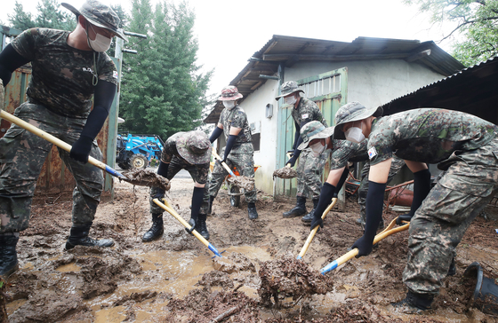 Soldiers on Tuesday clean up a landslide that occurred at a vacation resort in Yongin, Gyeonggi, due to heavy rains. [YONHAP]