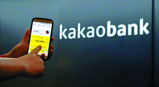 A person uses the Kakao Bank application in front of the bank's office. [YONHAP]