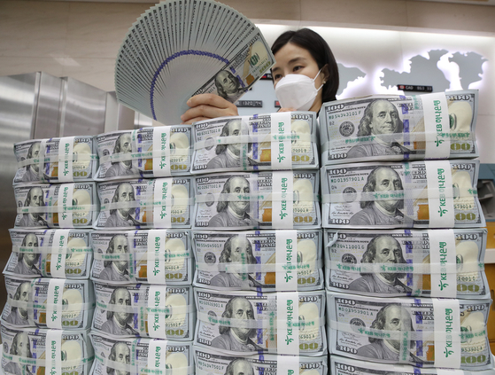 An employee organizes dollars at Hana Bank in Jung District, central Seoul, on Wednesday. According to data from the Bank of Korea, foreign exchange reserves came to $416.53 billion as of the end of July, up $5.8 billion from a month earlier. Korea's foreign exchange reserves have been increasing for four consecutive months. [YONHAP]