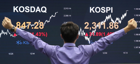 "A person cheers in front of the screen with the Kospi close Wednesday in the dealing room of KB Kookmin Bank located in the financial district of Yeouido, western Seoul. The final Kospi surpassed the 2,300 mark, driven by massive purchases by retail ""ant"" investors, closing at the highest level since October 2018. [NEWS1]"