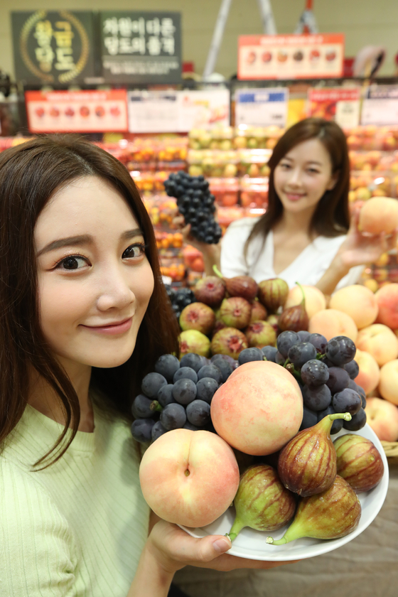 Models present seasonal fruits at Lotte Mart's Seoul Station branch in Jung District, central Seoul, on Wednesday morning. The discount store chain is holding events for sales of domestically cultivated grapes, peaches and figs from Aug. 6 to 12. [YONHAP]