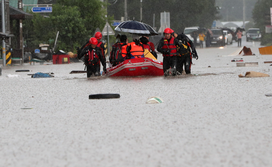 Rescue workers evacuate villagers in Cheorwon County, Gangwon, on Wednesday afternoon, after the region was hit by torrential rain. [YONHAP]