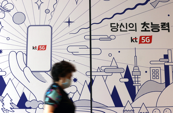 A citizen walks past a phone shop in central Seoul on Wednesday. [YONAHP]