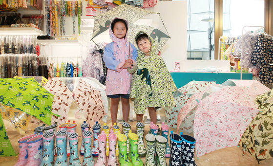 Children model rainwear such as umbrellas and raincoats in Lotte World Mall in Songpa District, southern Seoul, on Thursday. Rainwear brand HAS is offering up to 50 percent off its products for children. [YONHAP]