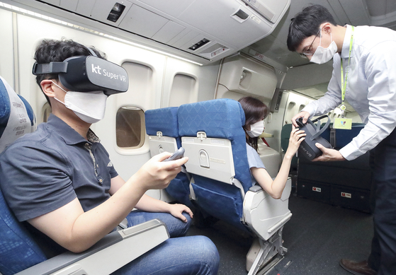 Customers experience immersive media on a Jin Air plane using Super VR, KT's VR platform. KT signed on Thursday a memorandum of understanding with Jin Air and Hanjin Information Systems & Telecommunication to launch in-flight VR services later this year. [YONHAP]