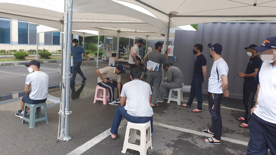 People wait to be tested for the coronavirus at a Covid-19 testing site in Cheongju, North Chungcheong, Wednesday, after health officials announced six Uzbek nationals in the city have tested positive this week. [YONHAP]