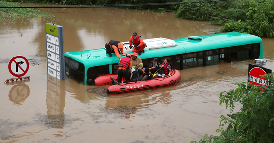 Rescue workers evacuate five people trapped in a bus amid a flood in Paju, Gyeonggi, on Thursday. [NEWS1]