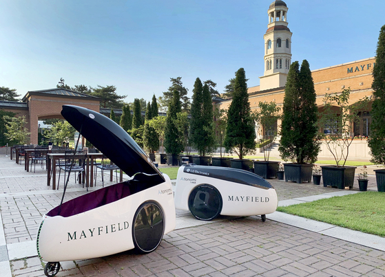 Two delivery robots by LG Electronics are seen on the terrace of the Mayfield Hotel in Gangseo District, western Seoul. LG announced Sunday the hotel will use the robots to serve customers in the outdoor terrace dining area. The electronics company previously launched a server robot called CLOi and a customer service robot at Incheon International Airport. [LG ELECTRONICS]