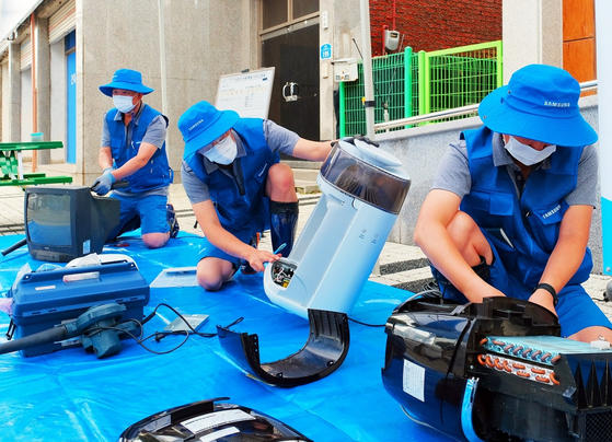 Samsung Electronics workers check flood-damaged electronic products to help victims of heavy rains in Yeoncheon, Gyeonggi. [YONHAP]