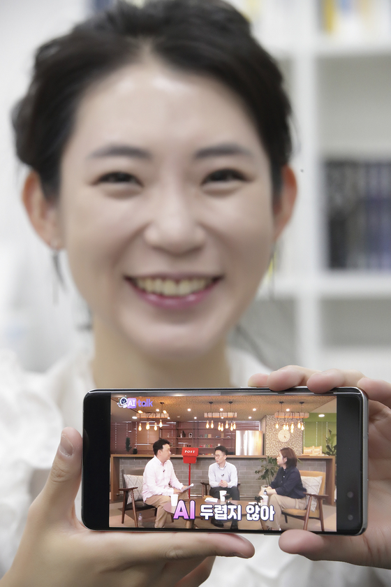 """A model holds a smartphone showing content offered as part of """"AI Study Week."""" The AI One Team, which is a collaborative endeavor between educational institutions and corporations, is holding the two-week """"AI Study Week"""" until Aug. 21 to provide online educational content aimed at raising awareness. [YONHAP]"""
