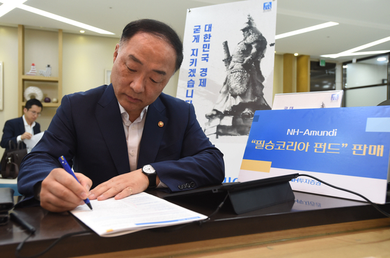 "Finance Minister Hong Nam-ki signs up for the ""Victorious Korea Equity Fund"" in September 2019. [MINISTRY OF ECONOMY AND FINANCE]"