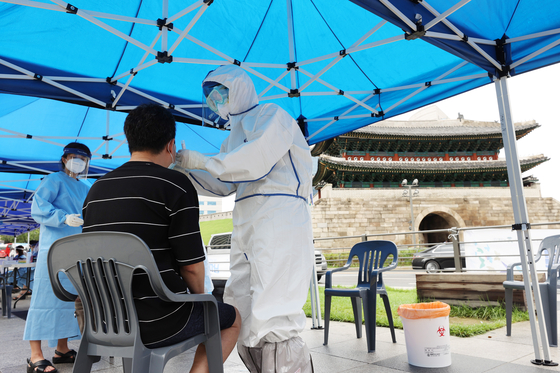 Health officials examine a man at a makeshift Covid-19 testing site at Namdaemun Market in Jung District, central Seoul, on Monday. Anyone who visited the market's Kennedy Complex from July 30 to Aug. 8 has been strongly recommended to be tested. [YONHAP]