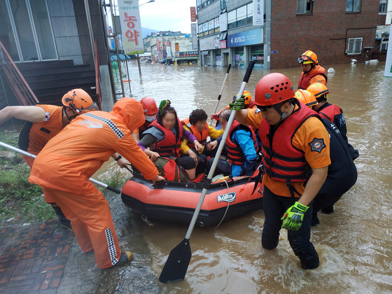 Firefighters rescue people in Gurye County, South Jeolla, on Saturday as the area was flooded by heavy rains. [NEWS1]