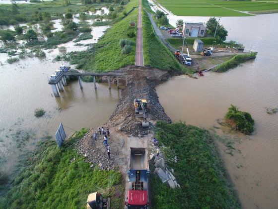 Restoration begins Monday after part of a dike along the Nakdong River in Changnyeong County, South Gyeongsang, was destroyed by heavy rainfalls.   [YONHAP]
