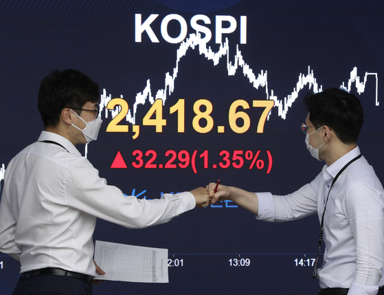 Two employees fist-bump in front of the screen with the Kospi close at a dealing room at KB Kookmin Bank in the financial district of Yeouido, western Seoul, Tuesday. [NEWS1]