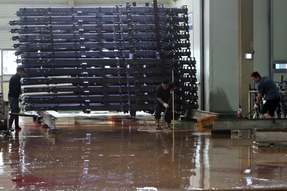 Employees of a car parts manufacturer at the Sochon Agricultural Industrial Complex in Gwangsan District, Gwangju, sweep off pools of muddy water on the factory floor. [YONHAP]