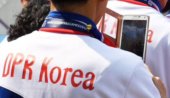 A North Korean athlete holds a cell phone during an event designed to celebrate athletes' entrance on Oct. 4 in 2018 ahead of the 2018 Asian Para Games held in Indonesia. [Joint Press Corps]