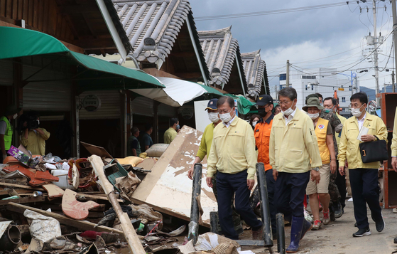 President Moon Jae-in visits a flood-stricken market in Gurye County, South Jeolla, on Wednesday to boost the merchants' spirits. [JOINT PRESS CORPS]