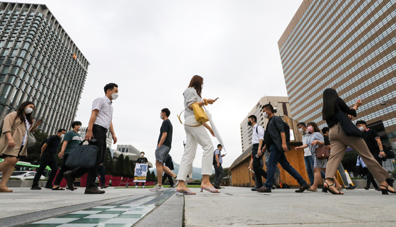 People walk to work in downtown Seoul on Wednesday morning without their umbrellas, as a prolonged rainy season showed a momentary lull.  [NEWS1]