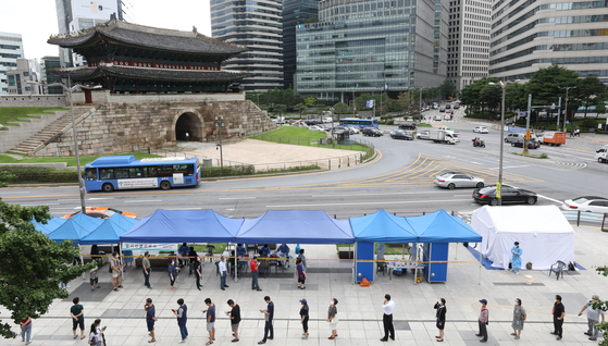 People line up at a Covid-19 testing site in Namdaemun Market, central Seoul, on Tuesday, after health authorities reported nine infections from merchants there. [NEWS1]