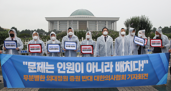 """Doctors member to Korean Medical Association, the largest union of doctors in Korea, protest in front of the National Assembly in western Seoul on July 23. Their banner reads, """"The problem is not in the numbers, it's in the distribution [of doctors]."""" [YONHAP]"""