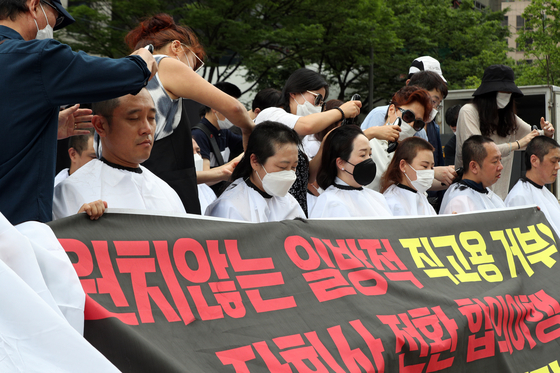Subcontracted workers from Incheon International Airport shave their heads at an event held in central Seoul on Thursday to show their disapproval of the airport's announcement that they must pass a test or go through the public recruiting system to be upgraded. [NEWS1]