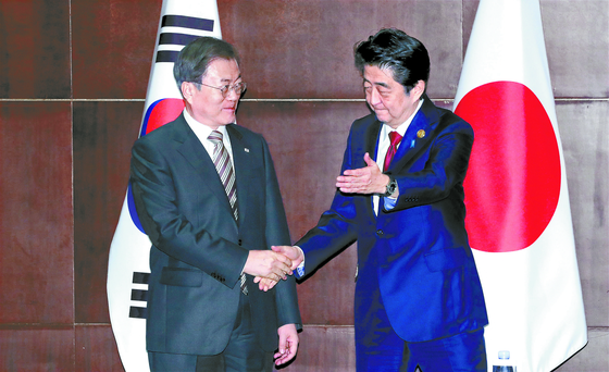 President Moon Jae-in and Japanese Prime Minister Shinzo Abe shake hands before a summit in Chengdu, China, on the sidelines of the 7th tripartite meeting among the three leaders on Dec. 24, 2019.