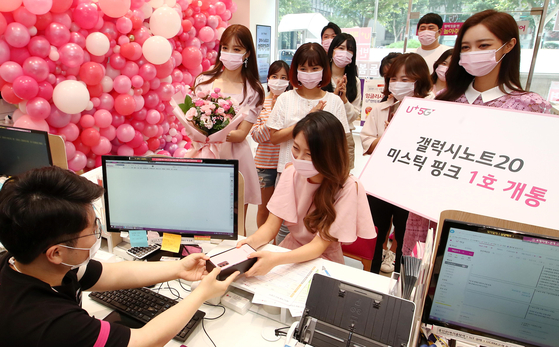 "The first customer in line for the ""Pink Me Up"" event at an LG U+ branch in Jonggak, central Seoul, registers her new mystic pink edition of the Samsung Galaxy Note 20 on Thursday morning. Customers registered on social media for a chance to buy the limited edition smartphone. [YONHAP]"