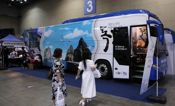 Attendees of the fifth Korea International Tourism Show at Kintex Exhibition Center on Thursday visit a bus to try a virtual reality tour of the Dokdo islets. The exhibition, which aims to vitalize the local tourism industry, is open to the public from Aug. 13 to Aug. 16. [YONHAP]