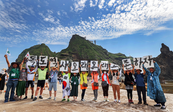 """A group of artists and cyclists visit the Dokdo islets on Thursday in advance of Liberation Day on Aug. 15. They hold hangul letters that read, 'Let's preserve the history of Dokdo eternally."""" [YONHAP]"""
