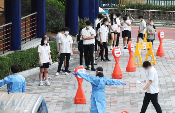 Students at Jukjeon High School in Yongin, Gyeonggi, line up to get Covid-19 tests Thursday after several freshman tested positive earlier this week. [YONHAP]