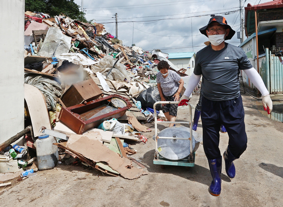 Rep. Joo Ho-young, floor leader of the United Future Party, participates in recovery work in flood-stricken Yongjeon Village in Namwon, North Jeolla, on Thursday. [YONHAP]