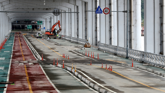 Workers on Thursday repair the Jamsu Bridge, which has been submerged under a flooded Han River since Aug. 2, to reopen the passage under Banpo Bridge in Seoul. [NEWS1]