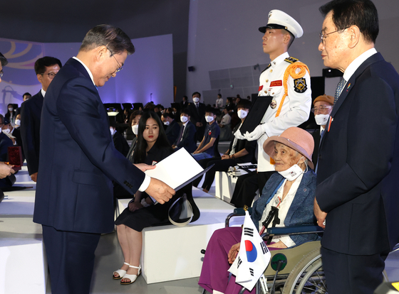 President Moon Jae-in, left, bestows a presidential award to the wife of an independence fighter on the 75th anniversary of Korea's liberation from Japanese rule on Saturday. [YONHAP]