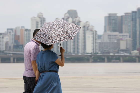A woman carries a sun parasol in Yeouido Hangang Park, western Seoul, on Sunday, as the record-long monsoon season ends and a heat wave begins. [YONHAP]