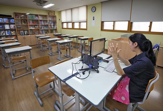 An English teacher prerecords her lesson in an empty classroom to upload online. [PARK SANG-MOON]