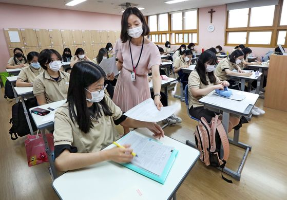 Kim Yu-na, an English teacher at Bakmun Girls' High School in Songdo, Incheon, hands out learning materials during a class on June 25. [PARK SANG-MOON]