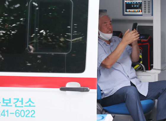 Pastor Jun Kwang-hoon of Saran Jeil Church is inside an ambulance of Seongbuk District Health Office on Monday. Despite his argument that he is free from infection, he tested positive for the coronavirus and was sent to an isolated ward.  [YONHAP]