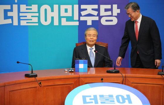 In this file photo, Kim Chong-in, center, sits for a press conference to announce his joining of the Democratic Party on Jan.15, 2016. Moon Jae-in, then the head of the party, stands next to him. [Shin In-seop]