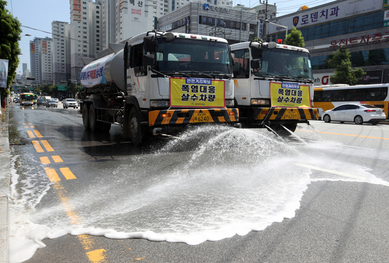 Water tank trucks spray water on a road in Gwangju on Tuesday as a heat wave scorches the city. [YONHAP]