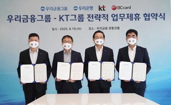 From left: Woori Bank CEO Kwon Kwang-seok, KT CEO Ku Hyeon-mo, Woori Financial Group Chairman Sohn Tae-seung and BC Card CEO Lee Dong-myun pose at an MOU signing ceremony on Aug. 19. [WOORI BANK]