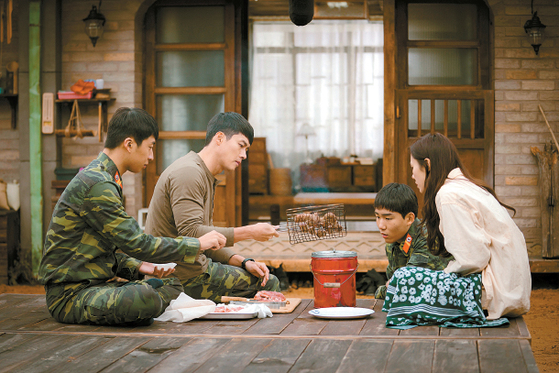 """Ri Jung-hyuk (played by Hyun Bin), second from left, grills some meat on charcoals at the request of Yoon Se-ri (played by Son Ye-jin), far right, in the drama series 'Crash Landing on You,"""" set in a small North Korean village.Ri Jung-hyuk (played by Hyun Bin), second from left, grills some meat on charcoals at the request of Yoon Se-ri (played by Son Ye-jin), far right, in the drama series 'Crash Landing on You,"""" set in a small North Korean village. [TVN]"""