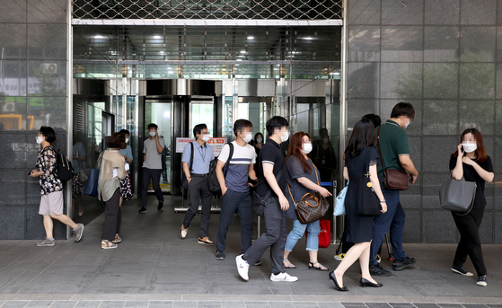 Civil servants at the main Seoul City Hall building in Jung District, central Seoul, evacuate Wednesday afternoon after a worker on the second floor tested positive for the coronavirus. [YONHAP]
